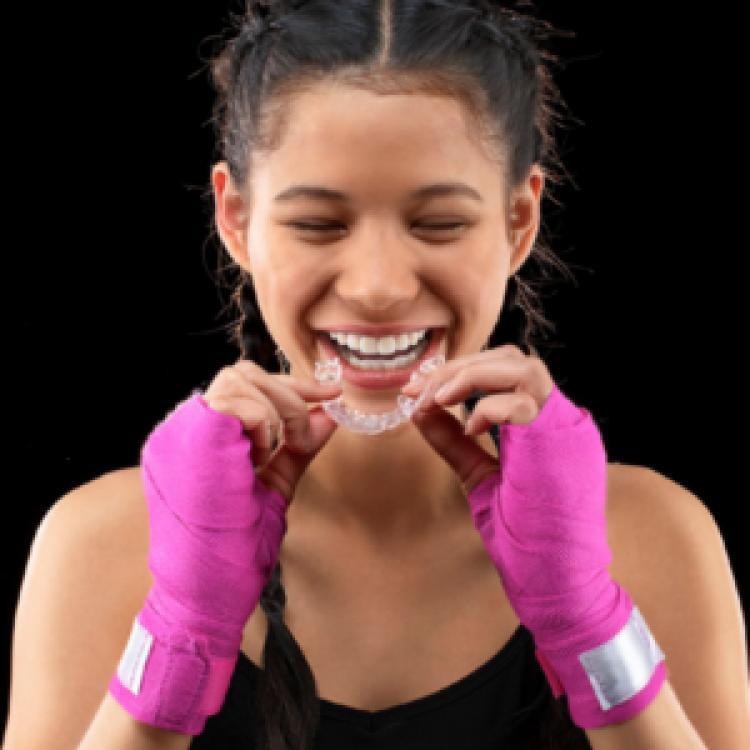 Boxeuse qui met un appareil Invisalign | Orthodontie des Laurentides à St Jérôme